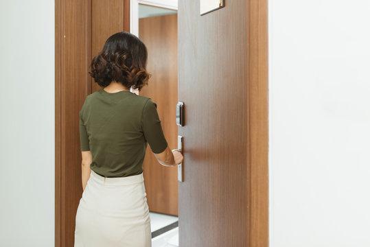 Woman Opens Door Of Apartment