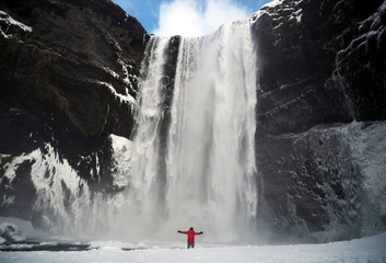 Man stands in front of the Skogafoss waterfall in Skogar