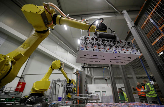 Robotic arms sort and load yogurts onto pallets at a distribution centre near Prague