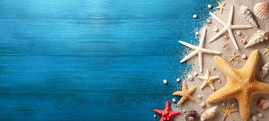 Autocollant pour porte Plage Seashell, starfish and beach sand on blue wooden background. Summer holiday banner. Top view.