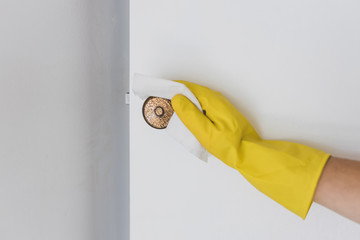disinfecting surfaces from bacteria or viruses sill-life, hand with glove cleaning door knob with disinfectant wet wipe