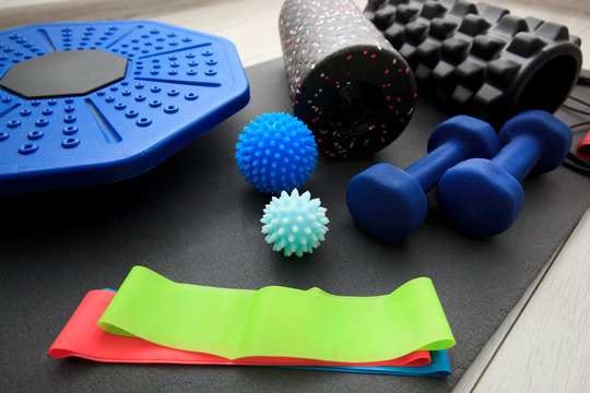 A lot of different fitness and sport accessories and equipment on the wooden floor at home