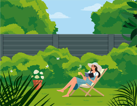 Girl with a cup reads a book while sitting on a deck chair in the garden.