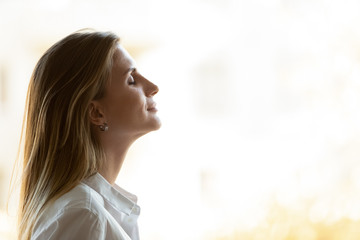 Side view close up head shot young mindful businesswoman breathing fresh air, managing stress at office. Calm peaceful millennial female manager, company owner or team leader meditating at workplace. Fotobehang