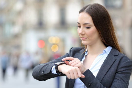 Business woman checking smart watch on city street