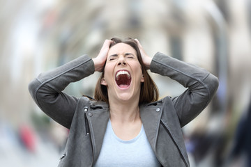 Stressed woman suffering anxiety attack on city street