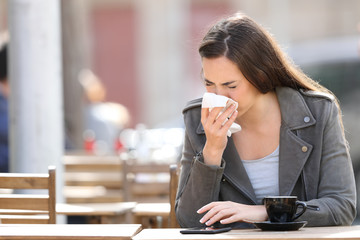 Woman blowing her nose with tissue on a coffee shop