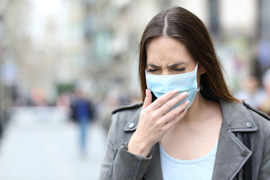 Sick woman with protective mask coughing on street