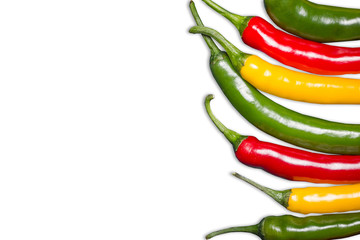 Color chili peppers. Hot spicy food ingredient. Red, yellow and green peppers isolated on white. Empty copy space vegetable background. Wall mural