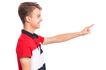 Fototapete - Portrait of teen boy pointing finger away at copyspace - side view, isolated on white background. Cute teenager smiling and pointing fingers at something. Happy child looking away - profile.