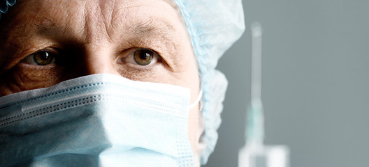 Mature male surgeon with syringe is preparing for injection