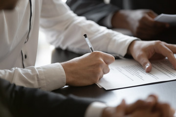 Close up young male employee manager customer hands signing paper contract after checking. Millennial investor client put signature at business agreement between partners. Editor making corrections.
