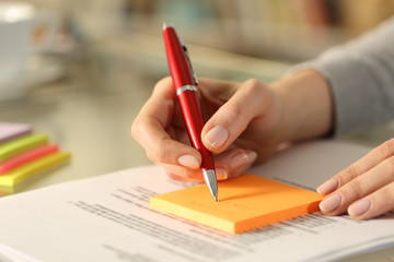 Woman writing to do list on sticky notes on a desk at home