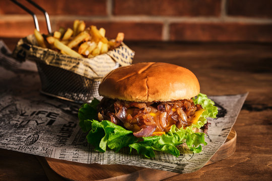 Burger with beef and caramelized onions on a wooden board. Cheeseburger with onion and beef. Juicy Delicious Homemade Burger.