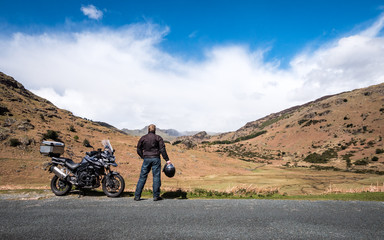 A motorcycle rider takes a break from his journey to appreciate the view in the English Lake District.
