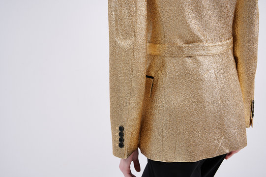Person in golden jacket. Luxury stylish classic clothes. Made of lurex thread. Individual tailoring.