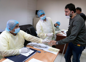 Expatriate, takes a coronavirus clearance certificate from a doctor, following the outbreak of the virus, at a health clinic in Subhan