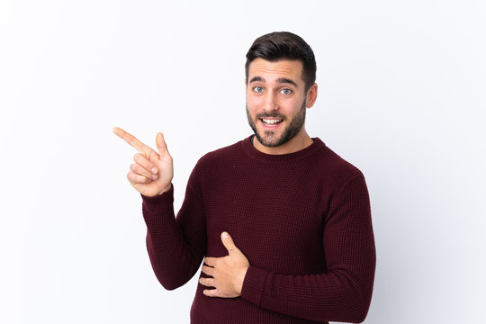 Young handsome man with beard over isolated white background pointing finger to the side