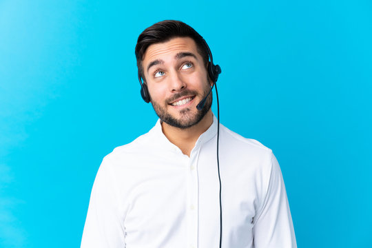Telemarketer man working with a headset over isolated blue background laughing and looking up