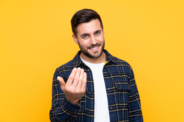 Young handsome man with beard over isolated yellow background inviting to come with hand. Happy that you came