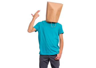 Fototapete - Portrait of teen boy with paper bag over head, doing gun gesture getting ready to shoot, isolated on white background. Child posing in studio.