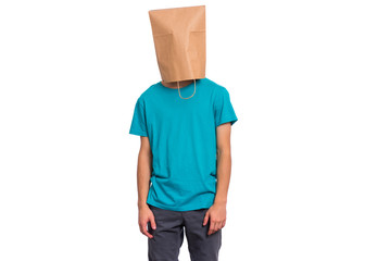 Fototapete - Portrait of teen boy with paper bag over head. Modest Teenager cover head with bag posing in studio. Shy Child pulling bag over head isolated on white background.