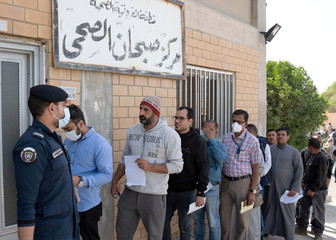 Expatriates are seen in line as they need to take a coronavirus clearance certificate, after returning from vacations, following the outbreak of the virus, at a health clinic in Subhan