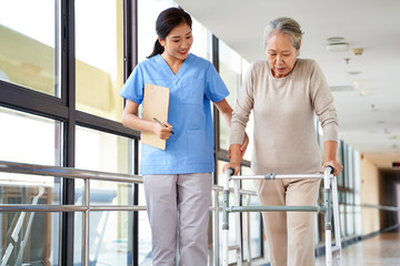 asian old woman walking with a walker in rehab center