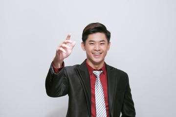 Smart casual man wearing black suit, pointing fingers to forehead standing on white background in studio