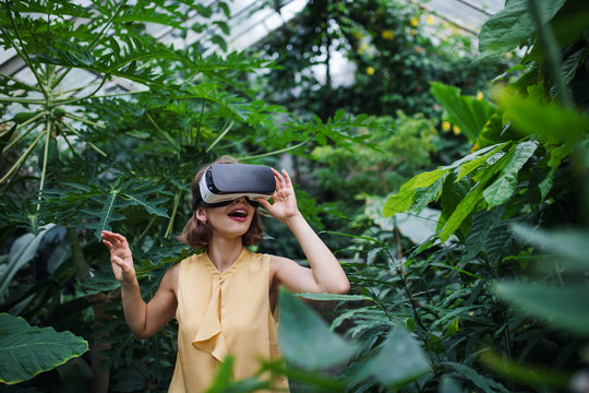 Front view of young woman standing in botanical garden, using VR glasses.