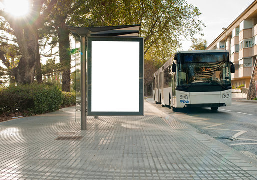 White blank vertical billboard at the bus stop on the city street. In the background of buses and roads. Sketch. Poster on the street next to the road