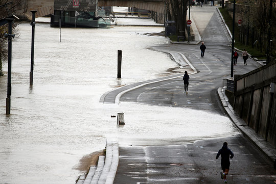 People run on the flooded docks of river Seine as water levels are expected to hit 4.3 metres today in Paris