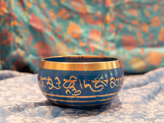 Haulerwijk - march 07 2020: Haulerwijk, The Netherlands. Blue and golden singing bowl made of seven metals with a wooden striker on an Indian scarf