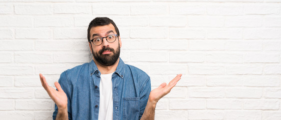 Handsome man with beard over white brick wall making doubts gesture