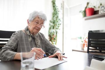 Serious senior Caucasian woman doing Alzheimer's disease or dementia clock drawing self assessment test in her apartment