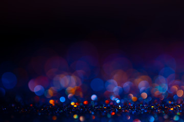 Festive bokeh glitters background, abstract blurred backdrop with circles,modern design wallpaper with sparkling glimmers. Black, blue and golden backdrop glittering sparks with blur effect