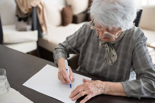 High angle view of a senior Caucasian woman doing Alzheimer's disease cognitive functions clock drawing self assessment test at home with positive results suggesting illness