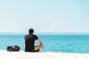 Keuken foto achterwand Tunesië young man traveler alone with backpack near him meditating looking into the ocean and enjoying the silence
