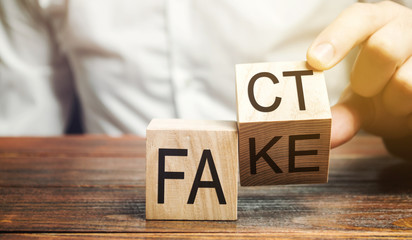 A man puts wooden blocks with the words Fact and fake. Concept of news and false information. Yellow press.