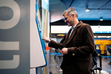 Side view of a business man buying an underground ticket.