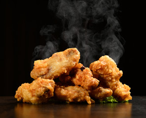 Foto op Canvas Kip Hot and spicy bbq chicken wings with with green salad leaf and steam smoke