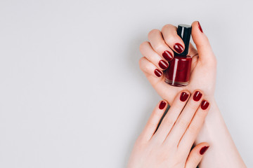 Beautiful dark red manicure with a bottle of nail polish in hands on a grey background. Procedures concept. Flat lay style.