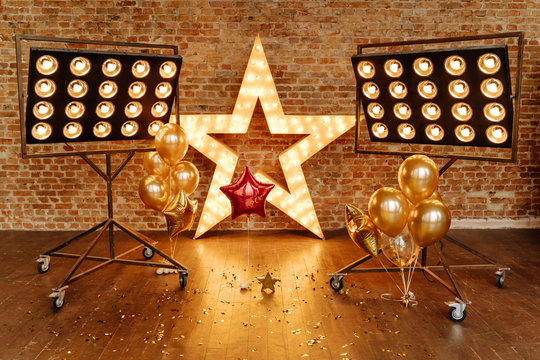 Star Frame with Lamps Decoration and Air Balloons. Scattered Confetti and Professional Illumination in Decorated Room Loft Style. Wooden Floor and Old Brick Wall on Background. Horizontal Photo
