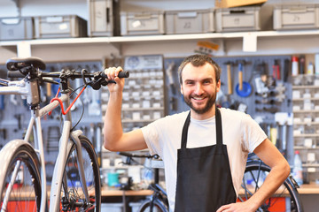 portrait of a friendly and competent bicycle mechanic in a workshop repairs a bike