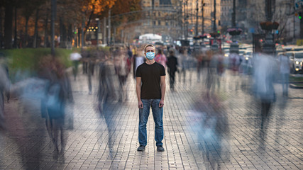 The young man with medical face mask stands on the crowded street Fotobehang