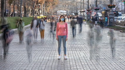 The woman with medical face mask stands on the crowded street Fotobehang