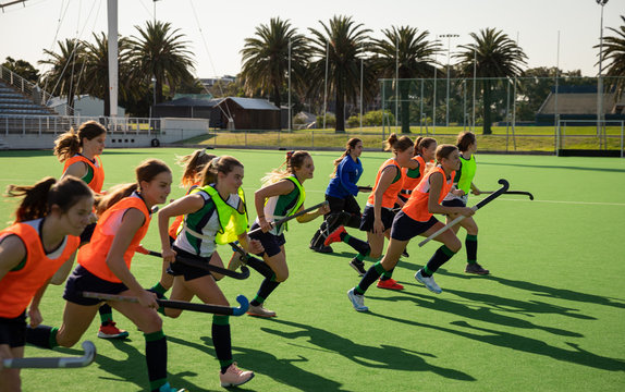 Hockey players running with hockey sticks on pitch