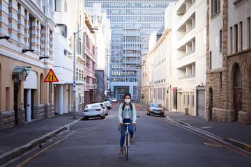 Woman biking in the street and wearing a Corona Virus face mask