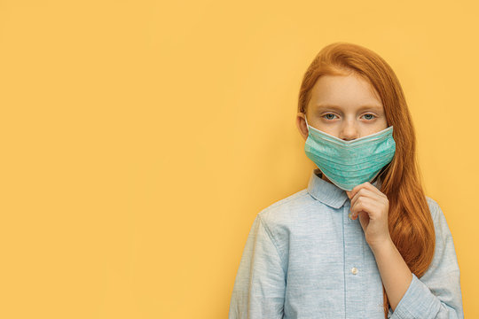portrait of ill caucasian red haired girl with protective mask on face, unhealthy girl suffer from fever, coronavirus. she protects others and herself with the use of medicaments and protective mask