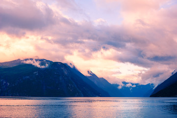 Beautiful sunset on the fjord in Norway. Mountains with pink clouds and their reflections in the water